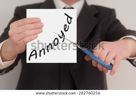 Annoyed, man in suit cutting text on paper with scissors