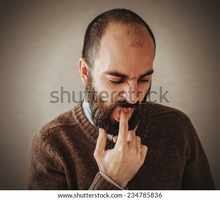 annoyed pissed off man with finger in mouth - stock photo