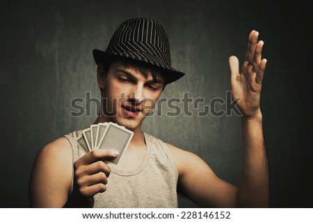 annoyed poker player hold cards in one hand and gesturing with the other hand, wearing hat and gray tank top, studio shot