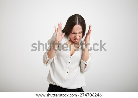 annoyed woman in formal wear hiding behind her hands over light grey background - stock photo
