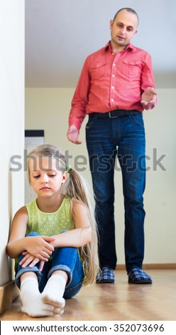 Annoying dad giving instructions to unhappy frustrated female child at home
