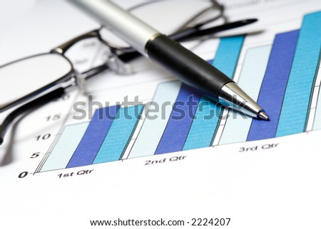 annual report with glasses and pen on graph