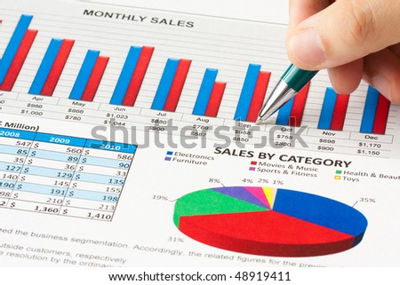 Annual sales report with a hand holds a ball pen - stock photo