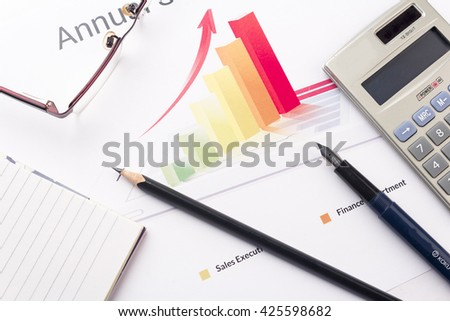 annual sales report with calculator pencils
