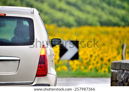 Anonymized car on bridge in countryside in rain - stock photo