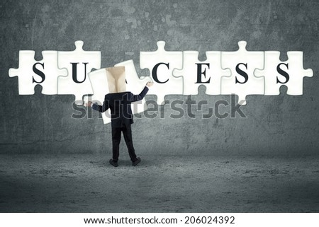 Anonymous businessman arrange jigsaw to compose success word