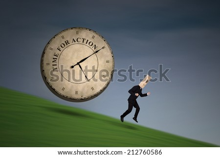 Anonymous businessman running chased by a big clock - stock photo