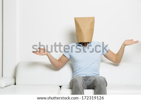 Anonymous clueless or innocent man with head covered by blank paper bag sitting on sofa, on white background. - stock photo