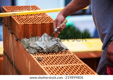 anonymous construction worker on a building site when building a house built a wall of brick. brick wall of a solid house. symbolic image for illegal work and bungling - stock photo
