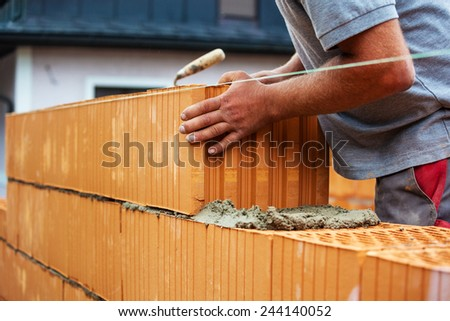 anonymous construction worker on a construction site in home building erected a wall of bricks. solid brick wall of a house. icon image for undeclared work and botch - stock photo