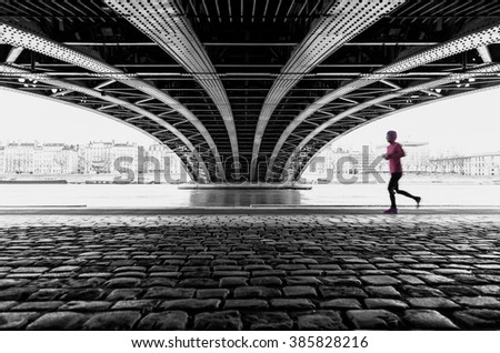 Anonymous female athlete running under a bridge in Lyon on a grey day. With motion blur and shallow focus. - stock photo