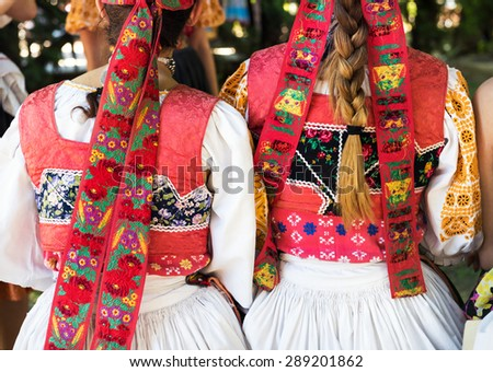 Anonymous girls in folklore costumes, back detail - stock photo