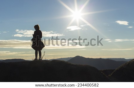 Anonymous silhouette female runner standing on a mountain top and checking her playlist on her music device as the sun flares in the background - stock photo