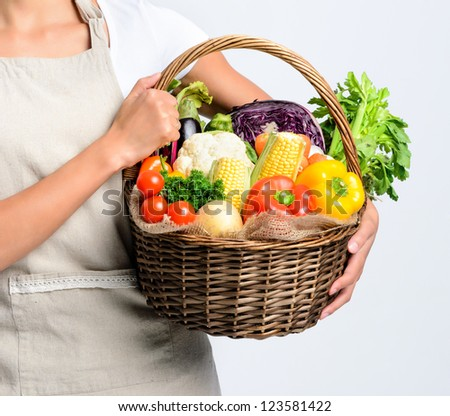 Anonymous young woman holding a basket full of fresh organic vegetable produce on grey background, promoting healthy diet and lifestyle - stock photo