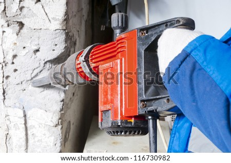 Another breaks the wall. Jackhammer in the worker hands. - stock photo