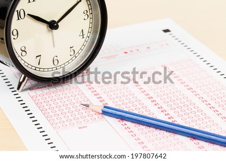 Answer sheet with pencil and alarm clock