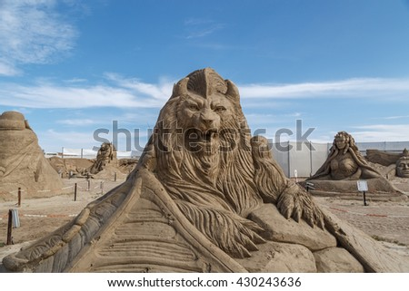 ANTALYA, TURKEY - APRIL 23, 2016 : View of big sand sculpture of mythological characters made in Lara Beach, Antalya for sandland project, on cloudy blue sky background. - stock photo