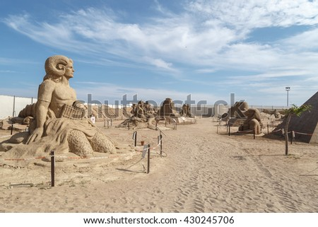 ANTALYA, TURKEY - APRIL 23, 2016 : View of big sand sculpture of mythological characters made in Lara Beach, Antalya for sandland project, on cloudy blue sky background.