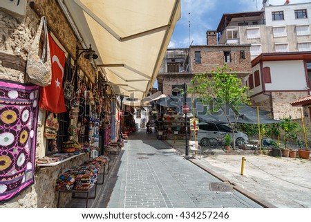 ANTALYA, TURKEY - APRIL 23, 2016 : View of Kaleici old town streets with small souvenir shops, on cloudy blue sky background.