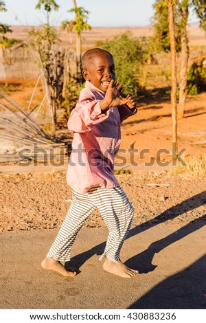 ANTANANARIVO, MADAGASCAR - JULY 3, 2011: Unidentified Madagascar boy runs happily in the street. People in Madagascar suffer of poverty due to slow development of the country