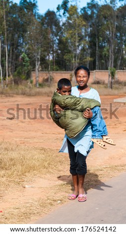 ANTANANARIVO, MADAGASCAR - JULY 1, 2011: Unidentified Madagascar girl carries her brother. People in Madagascar suffer of poverty due to slow development of the country