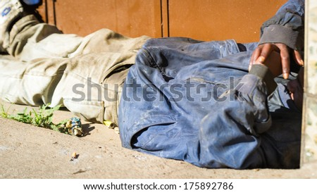 ANTANANARIVO, MADAGASCAR - JUNE 27, 2011: Unidentified Madagascar homeless man sleep on the road. People in Madagascar suffer of poverty due to the slow development of the country - stock photo