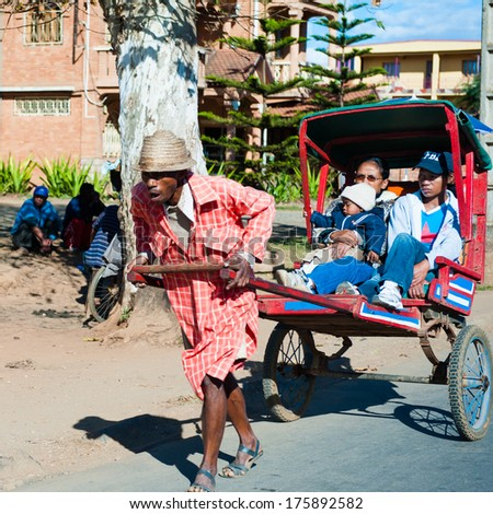 ANTANANARIVO, MADAGASCAR - JUNE 29, 2011: Unidentified Madagascar man carries  a transporting carriage with mother and children. People in Madagascar suffer of poverty due to the slow development  - stock photo