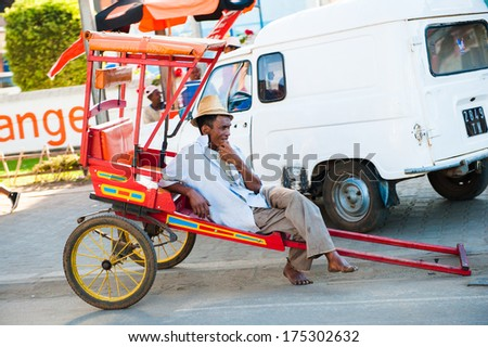 ANTANANARIVO, MADAGASCAR - JUNE 29, 2011: Unidentified Madagascar man sits on a carriage in the street. People in Madagascar suffer of poverty due to the slow development of the country - stock photo