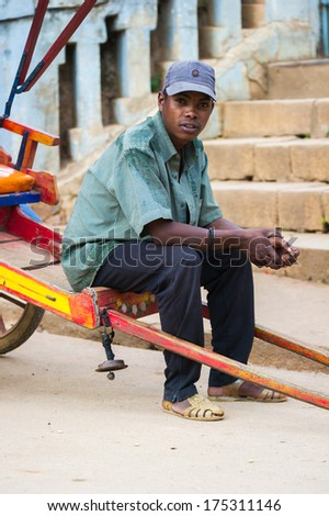 ANTANANARIVO, MADAGASCAR - JUNE 30, 2011: Unidentified Madagascar man sits on a red carriage. People in Madagascar suffer of poverty due to the slow development of the country - stock photo