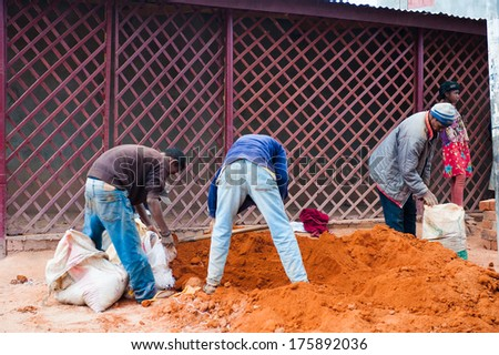 ANTANANARIVO, MADAGASCAR - JUNE 29, 2011: Unidentified Madagascar people get the sand. People in Madagascar suffer of poverty due to the slow development of the country