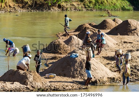 ANTANANARIVO, MADAGASCAR - JUNE 29, 2011: Unidentified Madagascar people take water from the river. People in Madagascar suffer of poverty due to the slow development of the country