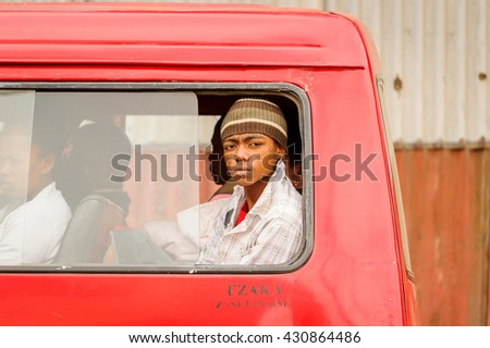 ANTANANARIVO, MADAGASCAR - JUNE 28, 2011: Unidentified Madagascar serious man looks out of a minivan window. People in Madagascar suffer of poverty due to the slow development of the country - stock photo