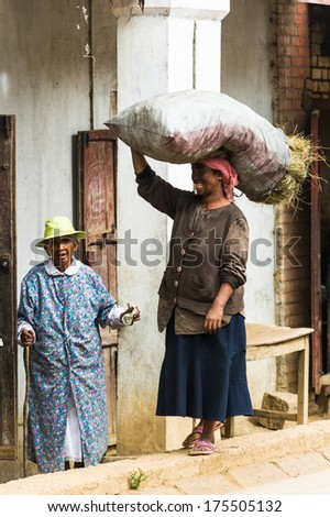 ANTANANARIVO, MADAGASCAR - JUNE 29, 2011: Unidentified Madagascar woman carries a big bag of hay. People in Madagascar suffer of poverty due to the slow development of the country