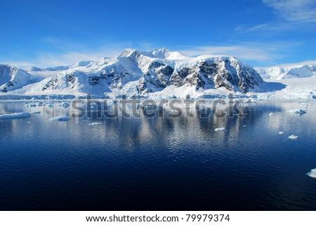 antarctic peninsula reflected in the blue ocean - stock photo