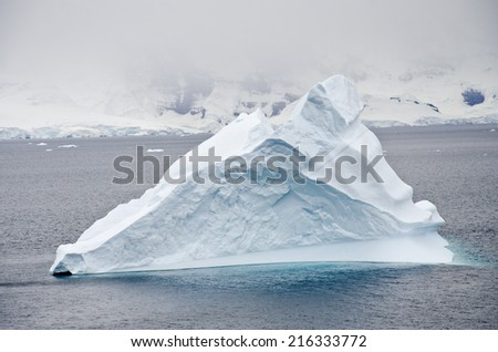 Antarctica - Non-Tabular Iceberg Drifting In The Ocean - Antarctica In A Cloudy Day - Global Warming - stock photo