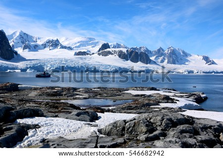 Antarctica water and snow-covered mountains with ship in background