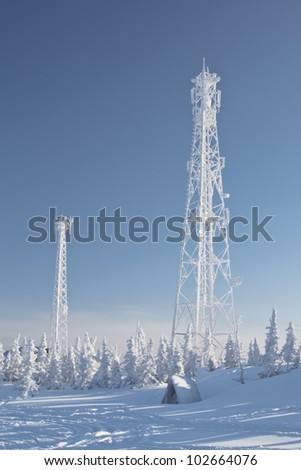 Antenna communications tower covered in snow in forest - stock photo
