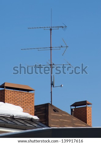 Antenna on the roof in sunny midday against bleu sky - stock photo