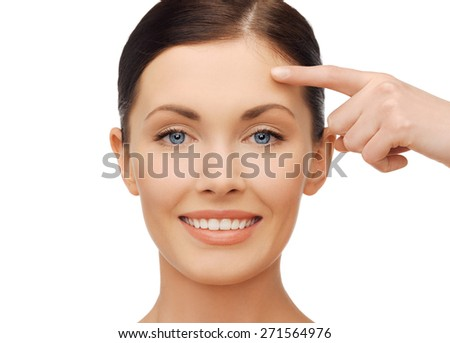 anti-aging concept - beautiful woman pointing to forehead - stock photo