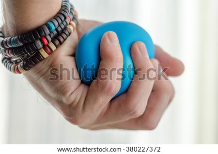 Anti-stress balls in hand, according to the window with bright sunlight - stock photo