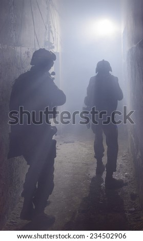 Anti-terrorist operation. Soldiers in full gear. Going up in smoke. Destroyed object. Back view. - stock photo