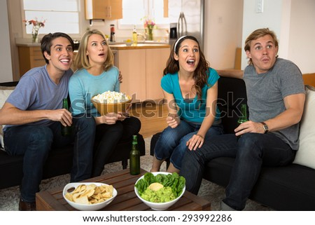 Anticipation and excitement during a sports game on tv with snacks at home - stock photo
