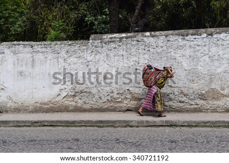 Antigua, Guatemala - October 30, 2015: A local woman walking from a local village to the centre of Antigua Guatemala, a UNESCO World Heritage Site founded in the 16th century.  - stock photo