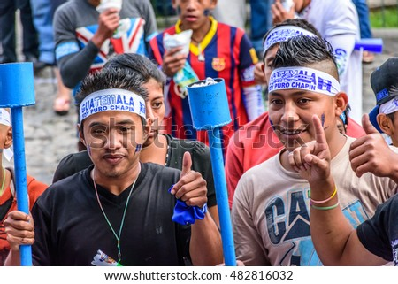 "Antigua, Guatemala - September 14, 2015: Locals wear headbands saying ""Soy puro Chapin"" (I'm pure Guatemalan) & carry torches during Guatemalan Independence Day celebrations"