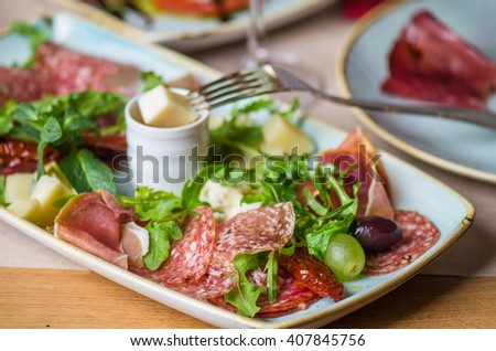 Antipasti - Italian appetizer of meat, cheese , arugula and grapes . Close- up of a plate on a restaurant table .  - stock photo