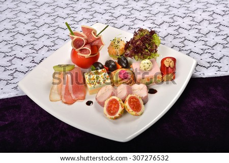 Antipasto and catering platter with different appetizers(fruits, vegetables, meats, cheeses)on white and purple background - stock photo