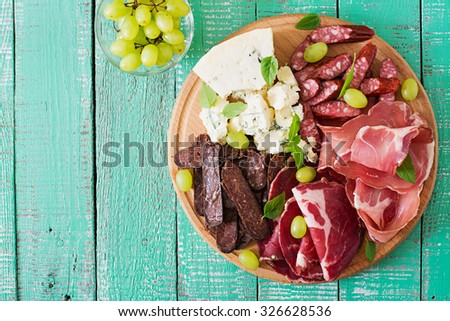 Antipasto catering platter with bacon, jerky, sausage, blue cheese and grapes on a wooden background. Top view - stock photo