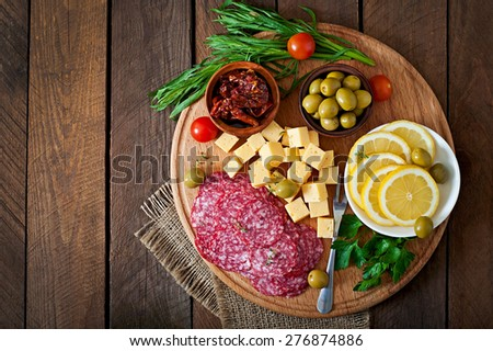 Antipasto catering platter with salami and cheese on a wooden background - stock photo