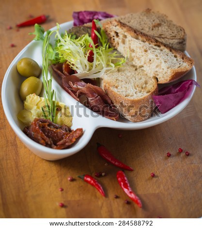 Antipasto. Dried tomatoes, olives, prosciutto and bread in a white plate. Shallow dof