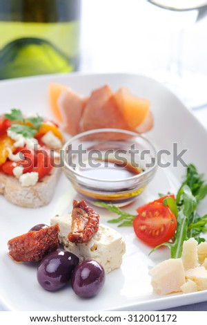 Antipasto; olives and sundried tomato, parma ham with rockmelon, toast with roasted mixed peppers and feta cheese, cubes of cheese and salad   - stock photo